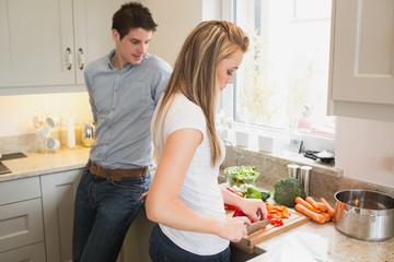 Man watching woman preparing vegetables