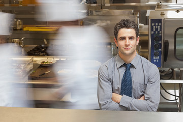 Waiter standing in busy kitchen
