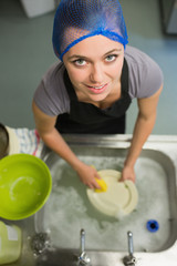 Smiling woman looking up from washing up