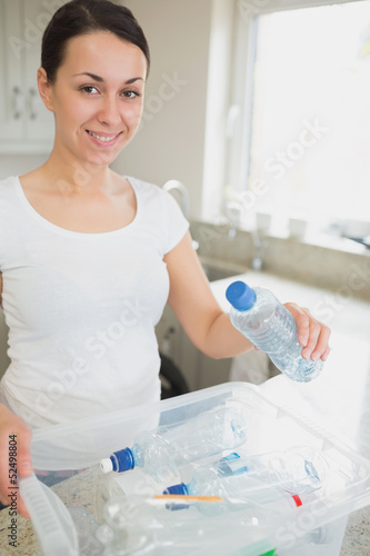 Woman throwing many bottles into recycling bin