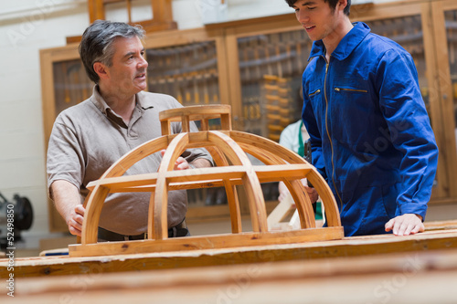 Teacher and student talking about a wooden frame