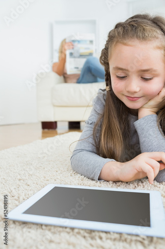 Girl using tablet with her mother reading the newspaper
