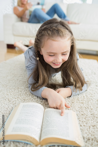 Girl reading book with her mother reading the newspaper