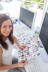 Smiling photo editor at work holding contact sheet