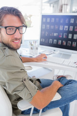 Smiling photo editor at his desk