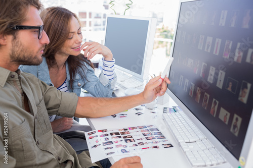 Photo editor pointing at thumbnail on screen with colleague
