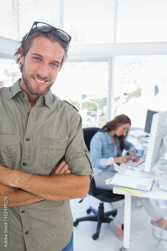 Man smiling in creative office with arms folded