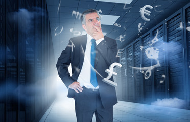 Businessman standing in data center with currency graphics