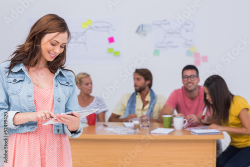 Woman using tablet with creative team working behind her