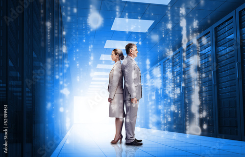 Business people standing back to back in data center