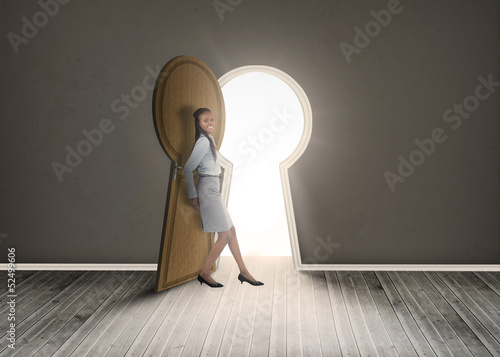 Businesswoman leaning against keyhole shaped doorway