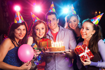 young company holds a cake with candles on birthday