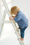Little boy learning to climb the ladder