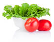 Bowl with fresh lettuce and two red tomatoes isolated on white b