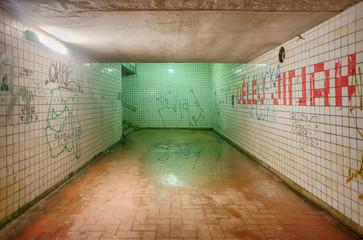 Abandoned and dirty subway tunnel painted by graffiti
