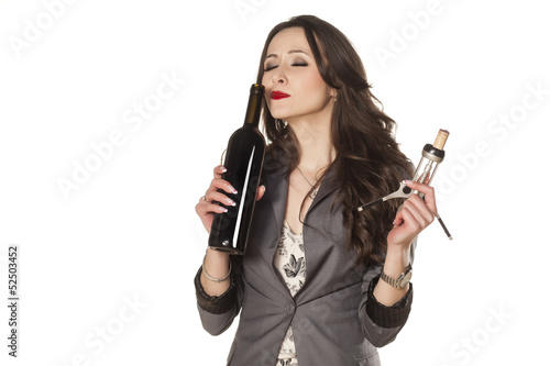 nice woman smells the wine from the bottle
