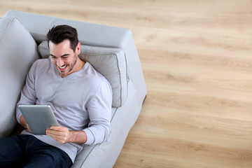 Upper view of man using tablet sofa