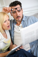 Couple reading news with horrified look