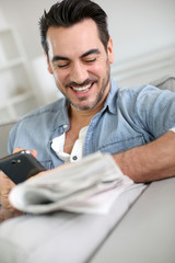 Man relaxing at home with newspaper