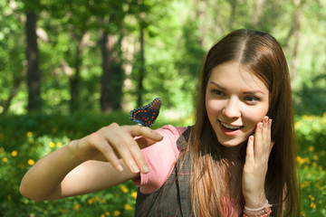 surprised beautiful girl holding butterfly on her finger at the