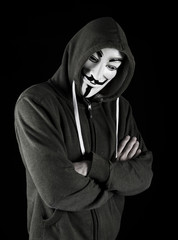 Hooded man wearing Vendetta mask