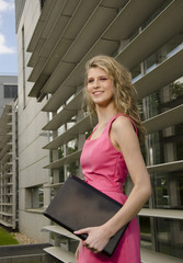 Young bussines woman with modern office in her background