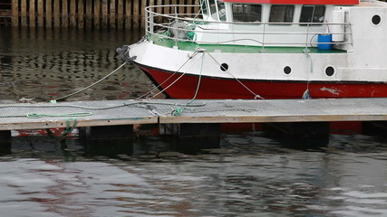 Small Norwegian fishing boat moored under the rain