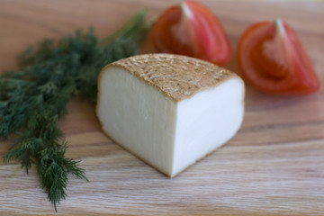 piece of smoked cheese with dill and tomatoes