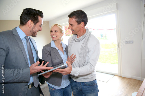 Middle-aged couple visiting house with salesman