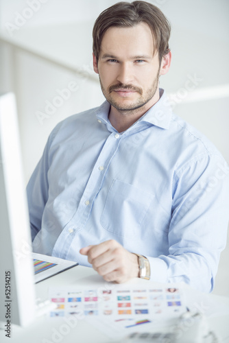 Handsome businessman sitting at the desk