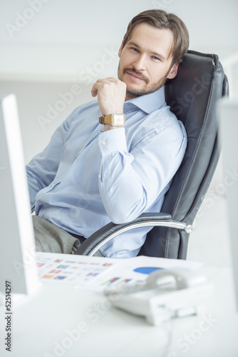 Handsome businessman sitting in chair in front of computer