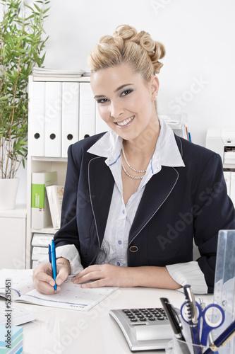 Lachende Geschäftsfrau blond - sitzend am Schreibtisch