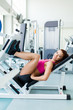 Attractive young fitness model works out on training apparatus