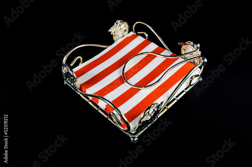 Napkin holder with red and white napkin over black background
