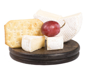 cheeses, cracker on the wooden board isolated on white