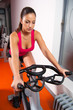 Beautiful fit girl exercising on the bicycle in the gym