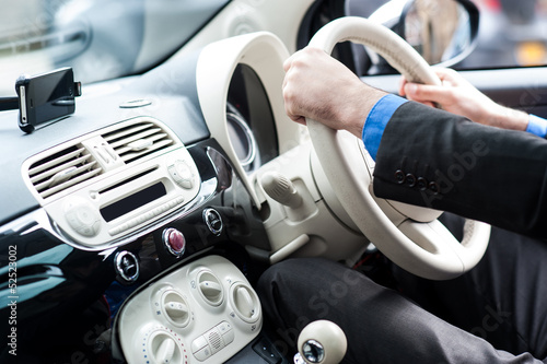Hands of a man on steering wheel of a car
