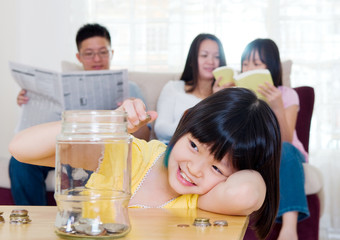Asian girl putting coins into the glass bottle