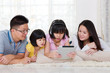 Asian family lying on the floor and using tablet computer