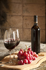 Copa de vino tinto y botella de vino, uvas.