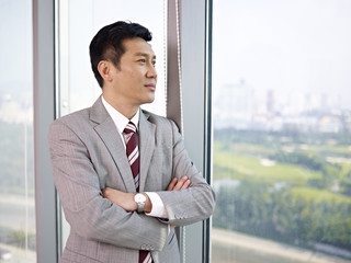 asian businessman standing by the window in office