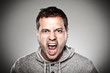 Young man screaming over grey background.