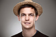 Portrait of a normal young man with straw hat on a grey backgrou