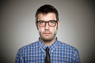 Portrait of a normal boy with glasses over grey background.