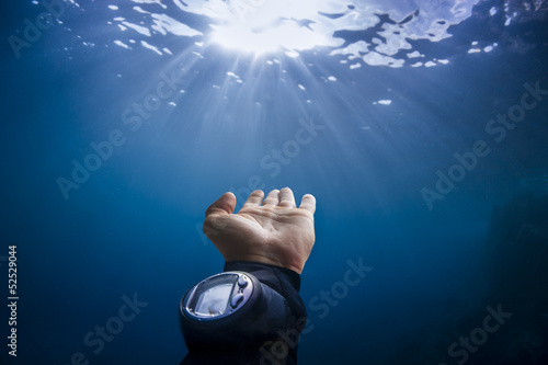 Scuba divers hand reaching out to sun light on blue background