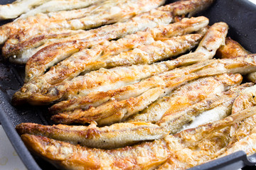 Sardines being prepared with sea salt on a barbecue grill  hotpl