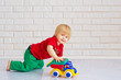 Cute little boy playing with his colorful toy car