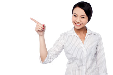 Happy young girl pointing at copy space area