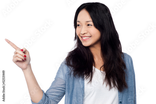 Young chinese girl pointing and looking outside