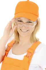 Freundliche junge Bauarbeiterin mit Schutzbrille